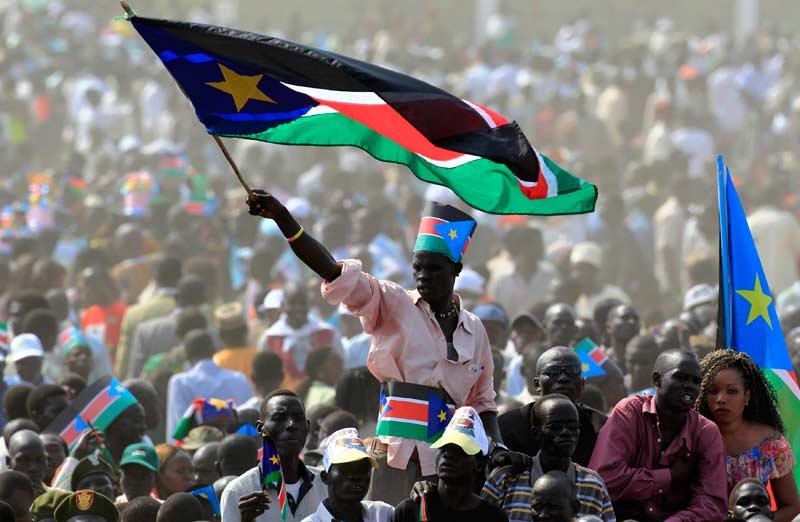 Muž mává státní vlajkou Jižního Súdánu, když se účastní oslav Dne nezávislosti v hlavním městě Juba 9. července 2011. Desítky tisíc jihosúdánských tančily a jásaly, když jejich nová země v sobotu formálně vyhlásila nezávislost, těžce vydělané oddělení od sever, který také ponořil zlomenou oblast do nového období nejistoty.